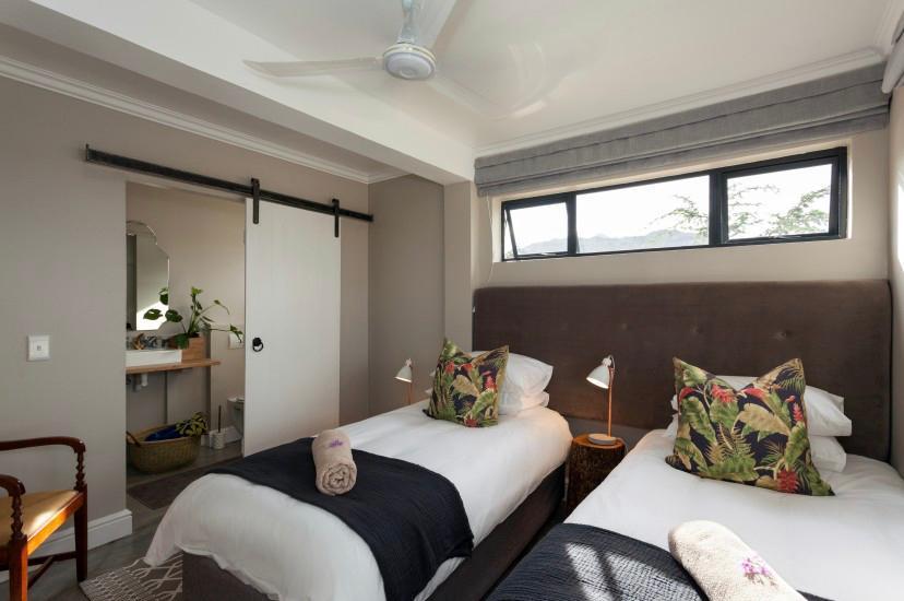 dormitorio con dos camas y un baño
